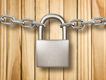 Locked padlock with silver chains  on wood background Royalty Free Stock Photos