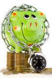 Locked piggy bank on coins Stock Images
