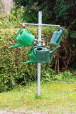 Locked public watering cans on a metal cross in the cemetery Stock Photos