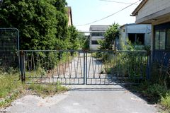 Locked rusted metal doors protecting entrance to abandoned factory with completely overgrown driveway surrounded with deserted bui stock photo