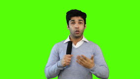 Locked-on shot of male TV reporter talking into a microphone on green background stock video footage