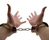 Locked Up. Photo of a mans wrists handcuffed with hands out stretched, isolated on white Royalty Free Stock Photos
