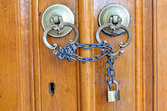 Locked wooden door. Old door knob and the door locked with chain Royalty Free Stock Image