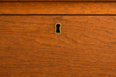 Locked wooden drawer. An old fashioned, locked wooden drawer.  The wood is mahogany with a reddish orange stain and a satin finish.  The lock is handmade brass Royalty Free Stock Images