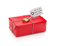 Locked wrapped christmas gift with red paper with label. Royalty Free Stock Photos