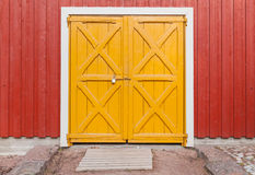 Locked yellow gate in red rural wooden wall Royalty Free Stock Photo
