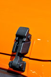 Locker of engine hood of cross and sports car. Locker of engine hood of a cross-country sports car in orange, which color and shape is beautiful, shown as Royalty Free Stock Photos