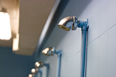 LOCKER ROOM SHOWERS. Gym locker room showers, empty and well lit Stock Photo