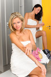 Locker room two sportive women applying lotion Stock Photo