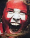 Lockern Sie mit der Schweizer Flagge auf, die auf dem Gesicht - Foto auf Lager gemalt wird Stockfoto