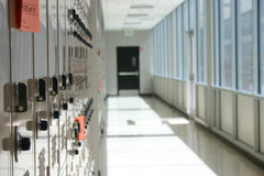 Lockers in hallway. Close-up shot of lockers in a row in hallway with exit door in center of shot royalty free stock image