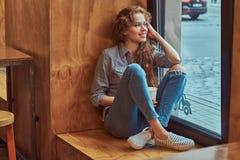 Lockig flicka för lycklig ung rödhårig man som bär tillfällig kläder och exponeringsglas som sitter på en fönsterfönsterbräda med arkivfoton