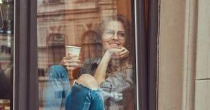 Lockig flicka för ung rödhårig man som bär tillfällig kläder och exponeringsglas som sitter på en fönsterfönsterbräda med ett tak arkivbilder