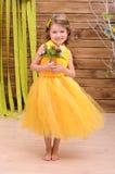 Lockig flicka i gul kappa med blommor royaltyfria bilder