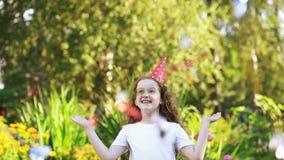 Lockig flicka i karnevalpartihatt med flygregnbågekonfettier arkivfilmer