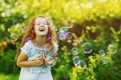 Lockig flicka med bubblor lyckligt barndombegrepp royaltyfria bilder