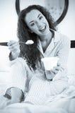 Lockig haired kvinna med smaklig yoghurt i säng Royaltyfria Foton