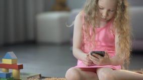 Lockig-haired liten flickamaskinskrivningmeddelande på smartphonen, genom att använda den moderna grejen lager videofilmer