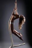 Lockig-haired ung kvinna som hänger på rep Arkivbild