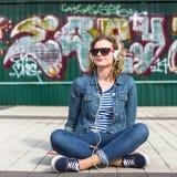 Lockig kvinna för ung Hipster som lyssnar till musik i staden Royaltyfri Fotografi