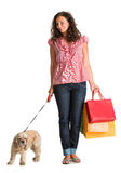 Lockig kvinna med shoppingpåsar och den amerikanska spanieln Arkivbilder