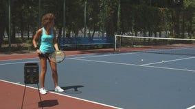 Lockig kvinna som slår tennisbollar stock video