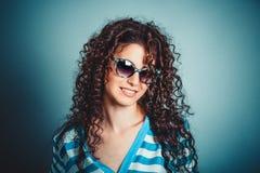 Lockig kvinnaflicka, i att le för solglasögon royaltyfri bild