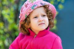 Lockig lite lady i den rosa hatten Royaltyfri Foto