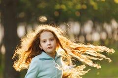 Lockig liten flicka med flygr?dh?rig manh?r royaltyfri foto