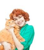 Lockig rödhårig flicka med en isolerad röd katt Royaltyfri Foto