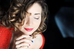 Lockig ung flicka som poserar i rött Royaltyfri Foto