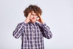 Lockig ung man som rymmer hans huvud med negativa sinnesrörelser på hans f Royaltyfri Bild