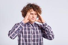 Lockig ung man som rymmer hans huvud med negativa sinnesrörelser på hans f Arkivfoto