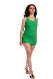 Lockig-vorangegangenes Mädchen im grünen Kleidschritt nach vorn Lizenzfreies Stockfoto