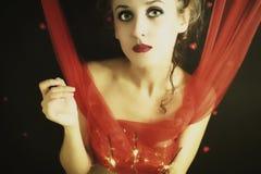 Lockige blonde Frau mit roten Farbbändern Stockbilder