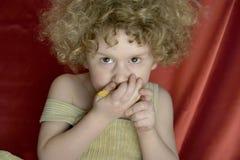 Lockiger Junge mit Corn Flakes Lizenzfreie Stockfotografie