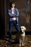 Lockiger Junge mit einem Hund Stockfoto