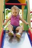 Lockiges behaartes blondes Mädchen am Spielplatz Lizenzfreies Stockfoto