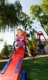 Lockiges behaartes blondes Mädchen am Spielplatz Stockfoto