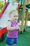 Lockiges behaartes blondes Mädchen am Spielplatz Stockbilder
