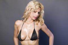 Lockiges blondes Mädchen im schwarzen Bikini Stockbilder
