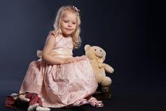 Lockiges Mädchen im rosafarbenen Kleid, das auf altem Koffer sitzt Lizenzfreies Stockbild
