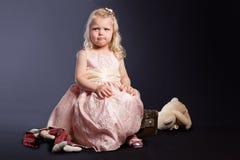 Lockiges Mädchen im rosafarbenen Kleid, das auf altem Koffer sitzt Lizenzfreie Stockfotos