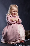 Lockiges Mädchen im rosafarbenen Mantel sitzt im alten Koffer lizenzfreie stockfotografie