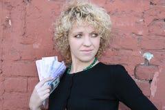 Lockiges Mädchen mit Geld Lizenzfreie Stockfotografie