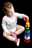 Lockiges Schätzchen, das auf dem Fußboden aufbaut einen Kontrollturm w sitzt lizenzfreies stockbild