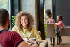 Lockigt flickasammanträde i kafé med hennes pojkvän och att dricka kaffe som äter bakar ihop royaltyfri fotografi