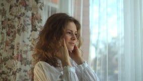 Lockigt hår för flicka som lyssnar till musik i hörlurar på fönstret lager videofilmer