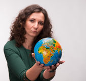 Lockigt kvinnainnehav ett jordklot Arkivfoton
