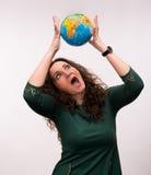Lockigt kvinnainnehav ett jordklot Arkivfoto